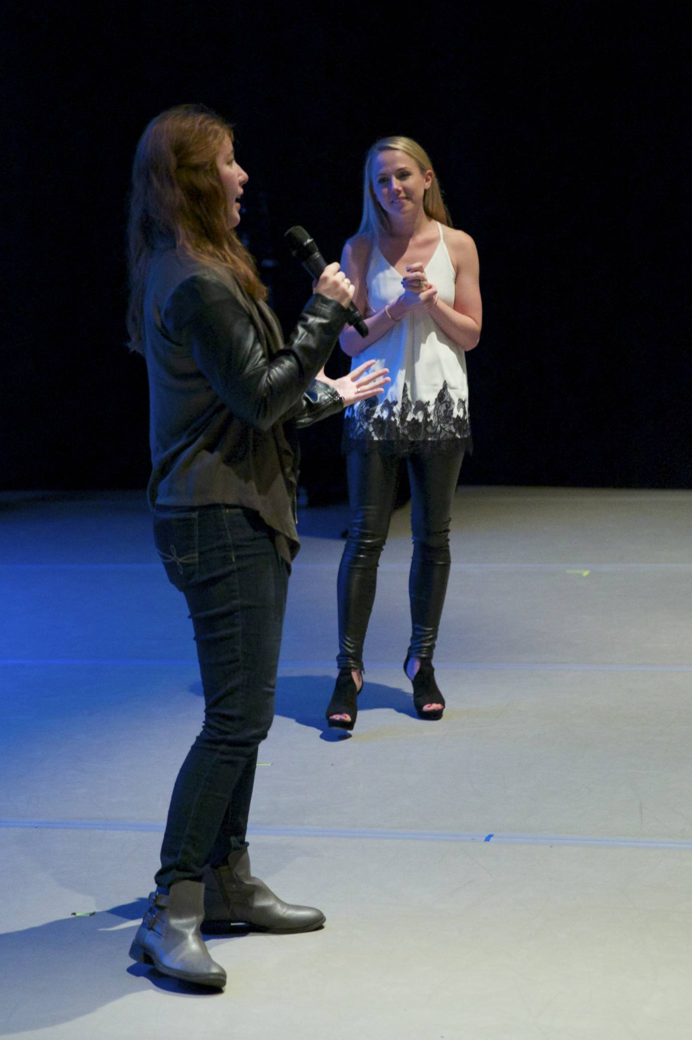 Two women stand on stage and talk about MorDance's performance