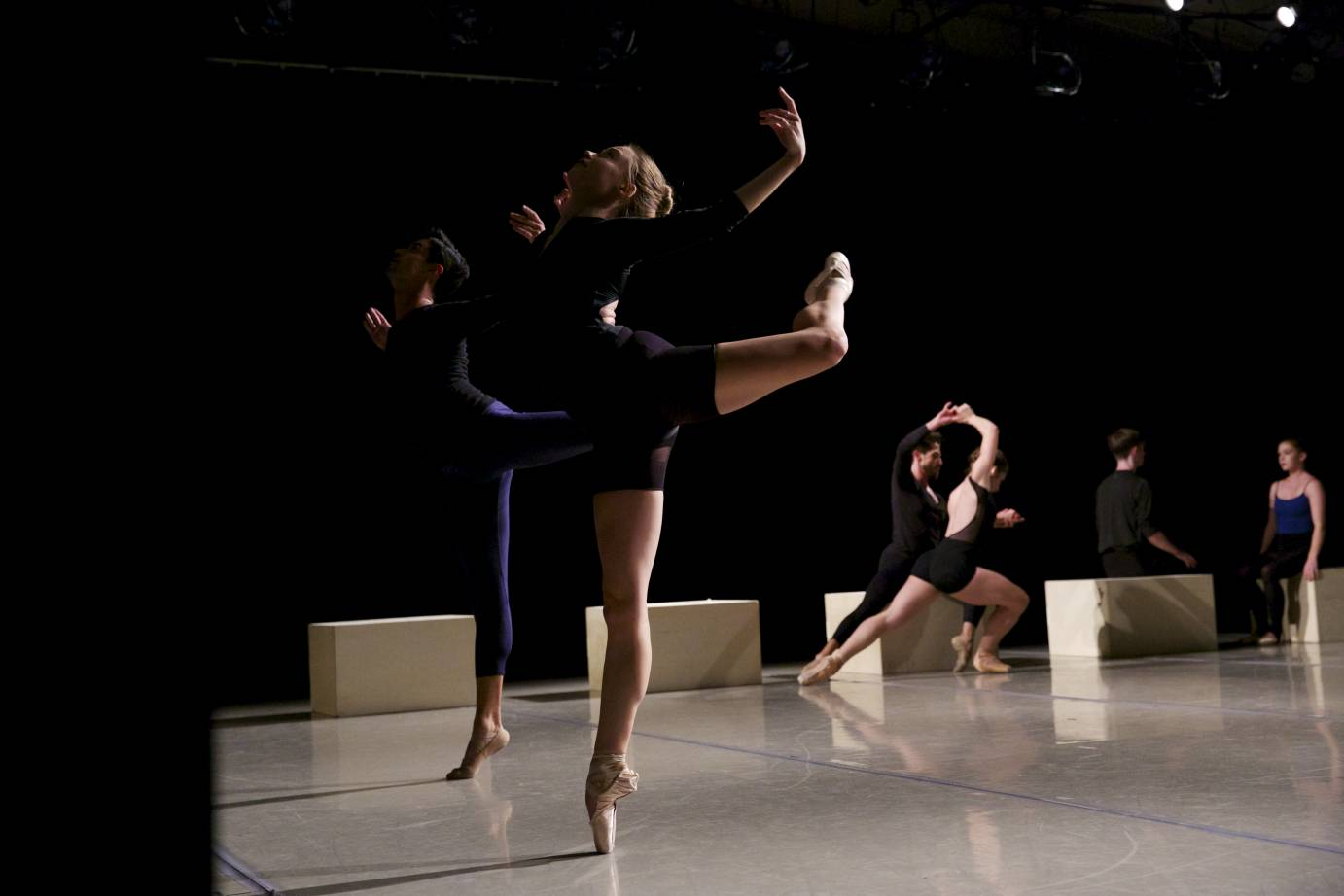 Two people pose in attitude in relve on one side of the side while other dancers lunge and sit in the background.