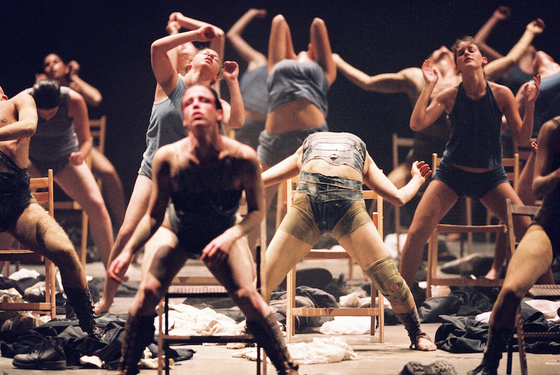 A group of dancers hover over chairs. Shoes and clothers are strewn about. One dancer assumes a dramatic back end with her legs wide apart.