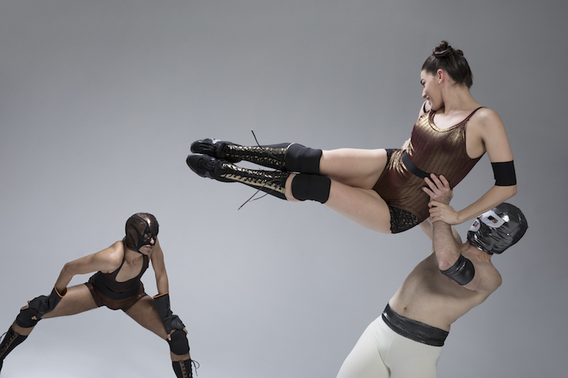 A man in a wrestling mask lifts up a woman in a gold leotard. Her legs, in knee-high boots, kick towards another dancer in the background who is also wearing a wrestling mask.
