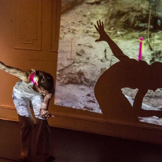 A dancer performs in front of a projected video. Its image projects onto her body.