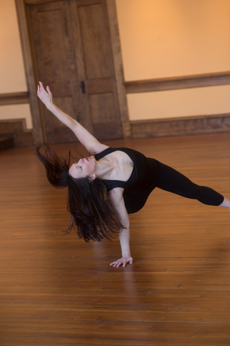 A dancer is in a lunge with one arm supporting her on the ground and one hand reaches for the sky. Her long brown hair flies in response.