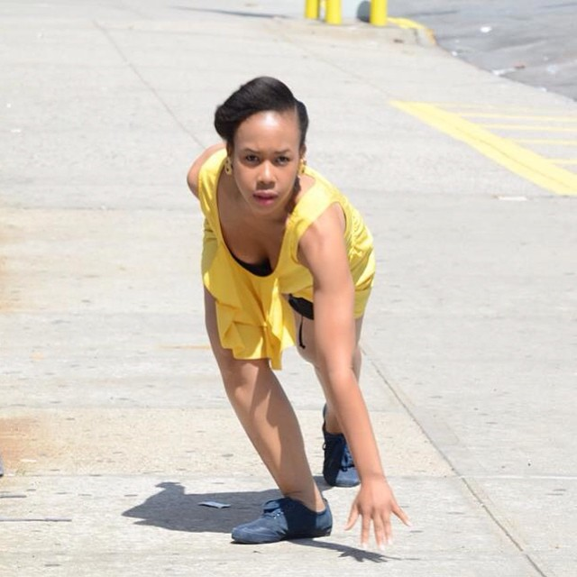 A dancer in a yellow dress looks directly at the contest, looking as if she is about to take off in a sprint