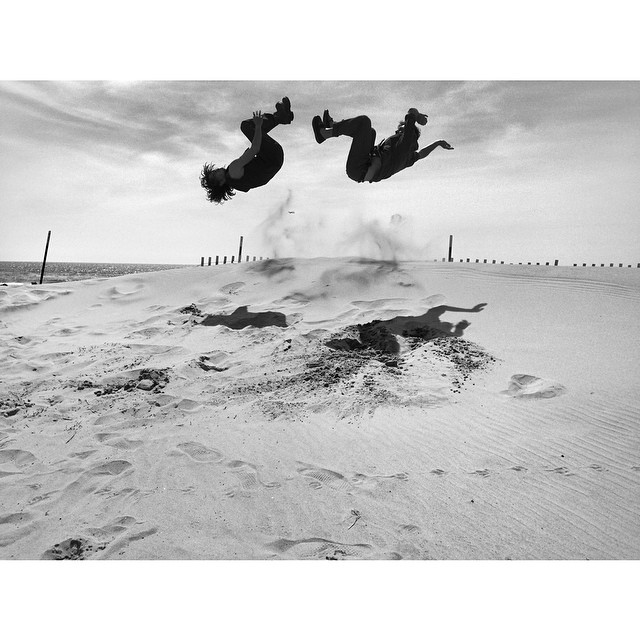 Two dancers jump in the air on the beach as if they are in midst of flipping