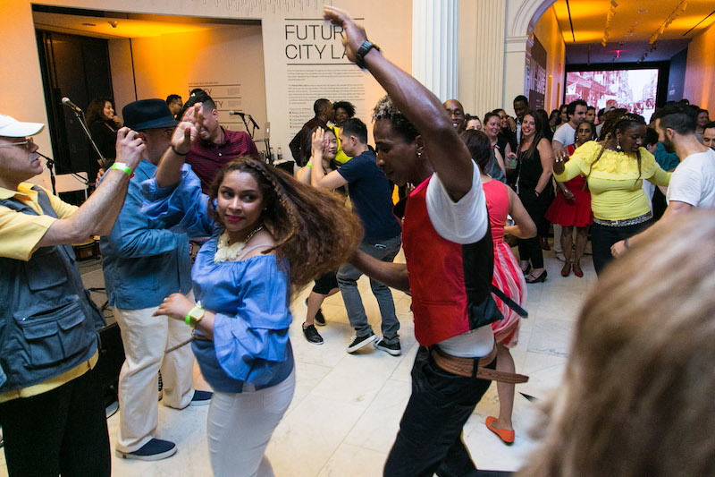 A crowd of people dance in the atrium of the Museum of the City of New York. A woman in blue blouse and white jeans is in the foreground. Her hair fans out as a man in a red vest spins her.