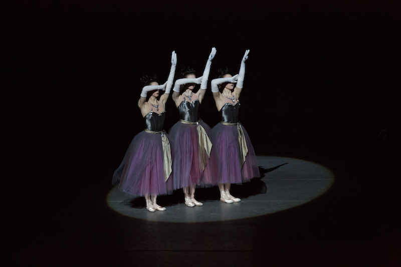Three dancers in purple tutus and slinky white gloves cover their eyes with their forearm while their other arm extends above them