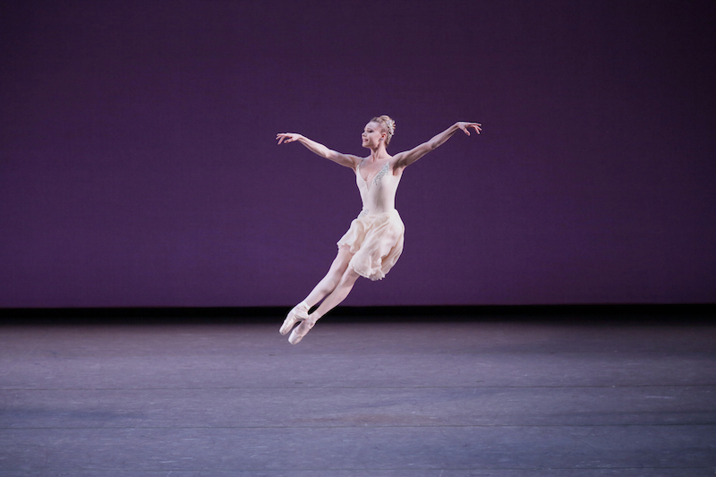 Sara Mearns is airborn, both of her legs beat together creating a scissor motion