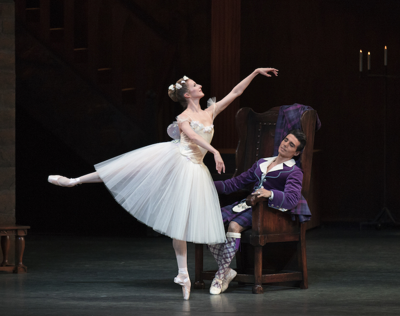 Sterling Hyltin performs a Romantic style arabesque on point while Joaquin De Luz dressed in a bright purple kilt lazily sits on a throne