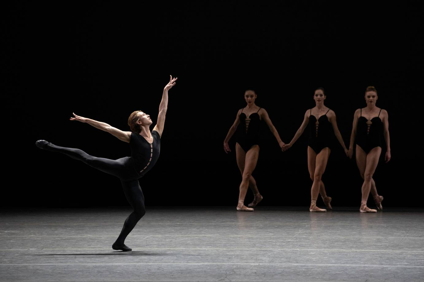 A man in amplified arabesque is in front of three women