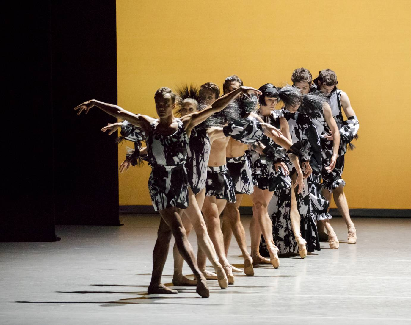 Eight dancers in a line that stretches from downstage to up