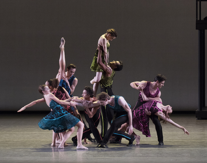 A mass of colorfully colored dancers strike virtuosic poses.