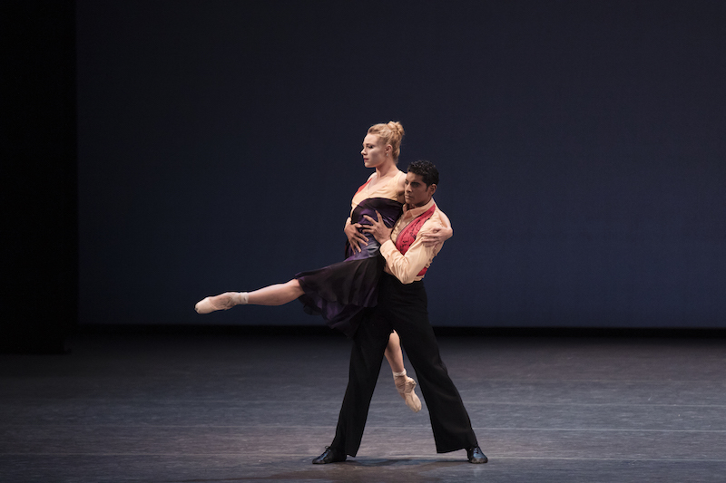 Amar Ramasar lifts Sara Mearns from her waist. Her left leg outstretched in front of her, Sara holds onto Amar's shoulder. She looks like she's floating in midair.