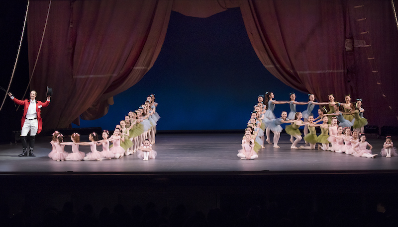 Child dancers in pastel colored tutus pose in cascading linear formations with their hands on one another's shoulders. Ask la Cour in a red tail coat and top hat stands off to the side of them.