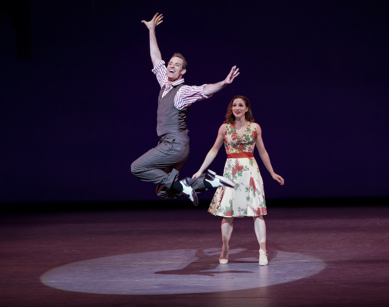 A man in a vest, wing-tipped shoes and slacks jumps into the air. A woman in a flowered dress grins behind him.