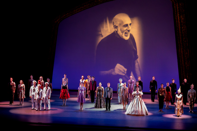 Dancers stand in costumes, including sailor suits and evening gowns, in front of a video projection that features an image of the late Jerome Robbins