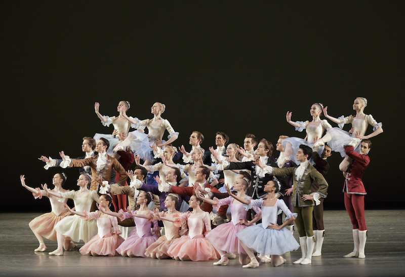 The cast of The Goldberg Variations knee and stand in a big formation. They gesture with their right hand.