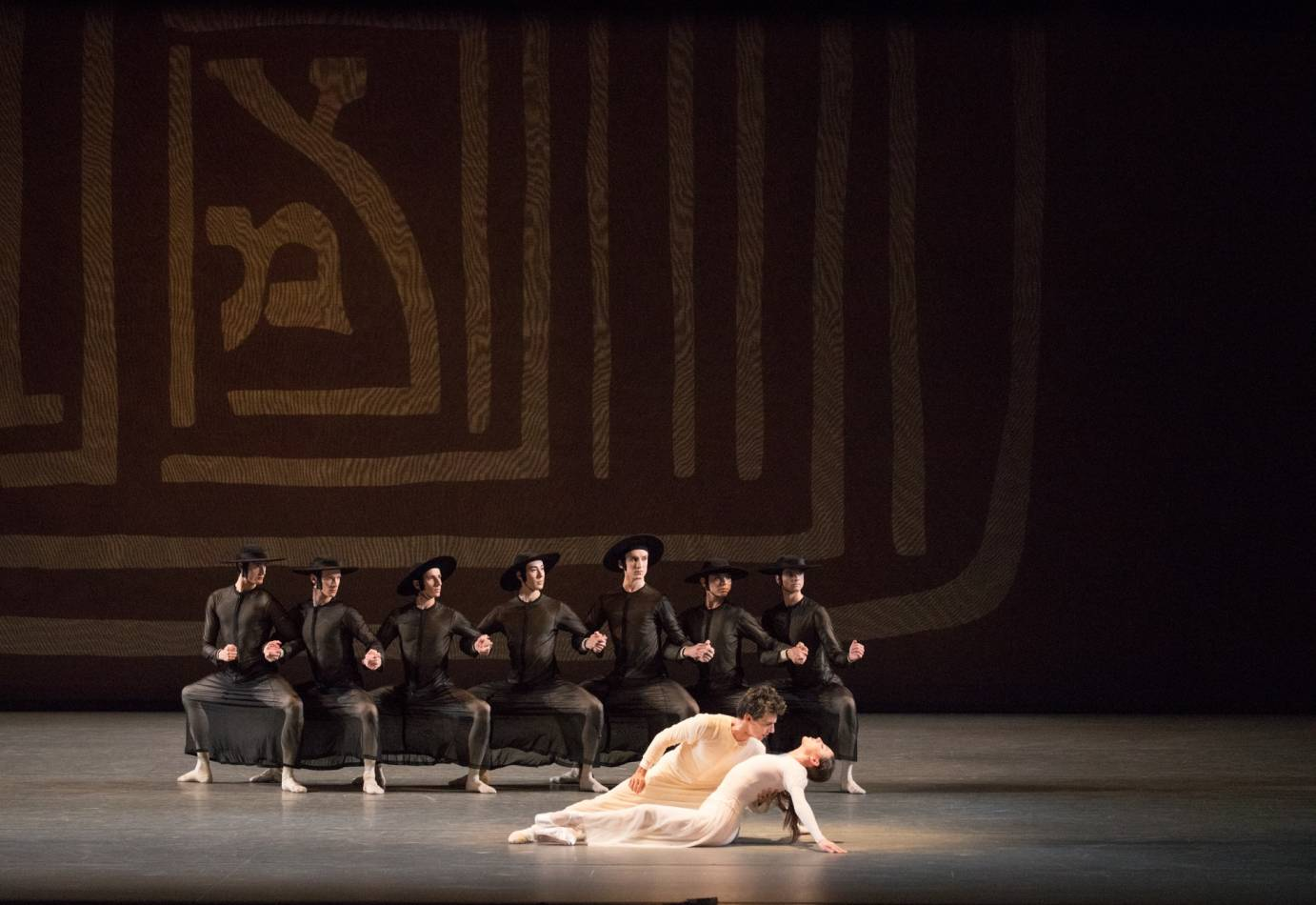 A line of dancers in deep second positions. A dancer lines in front of them.