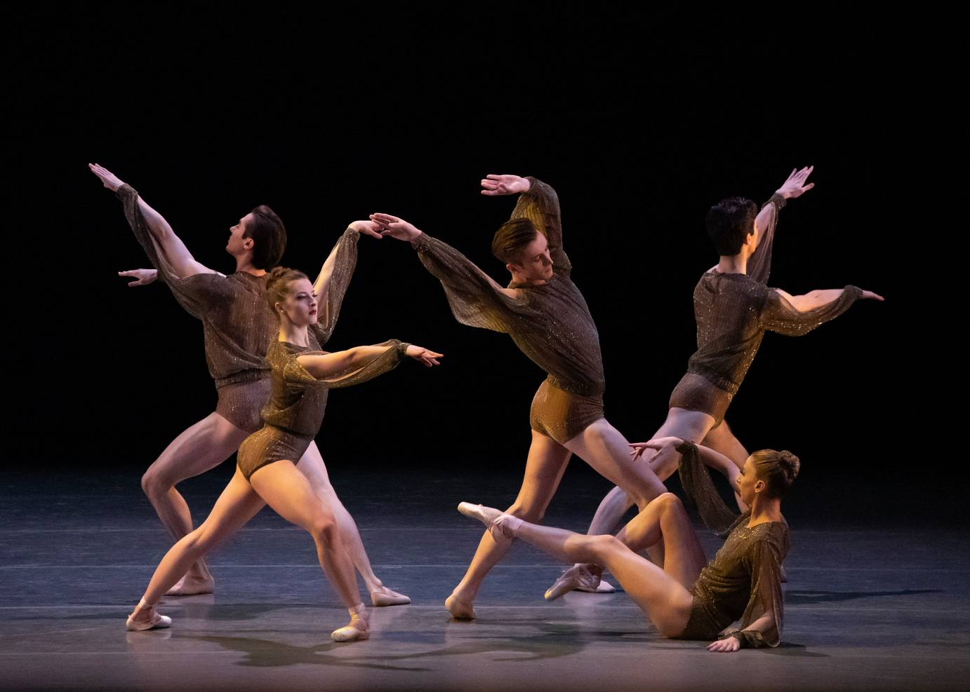 Dancers in brown pose with their arms extended