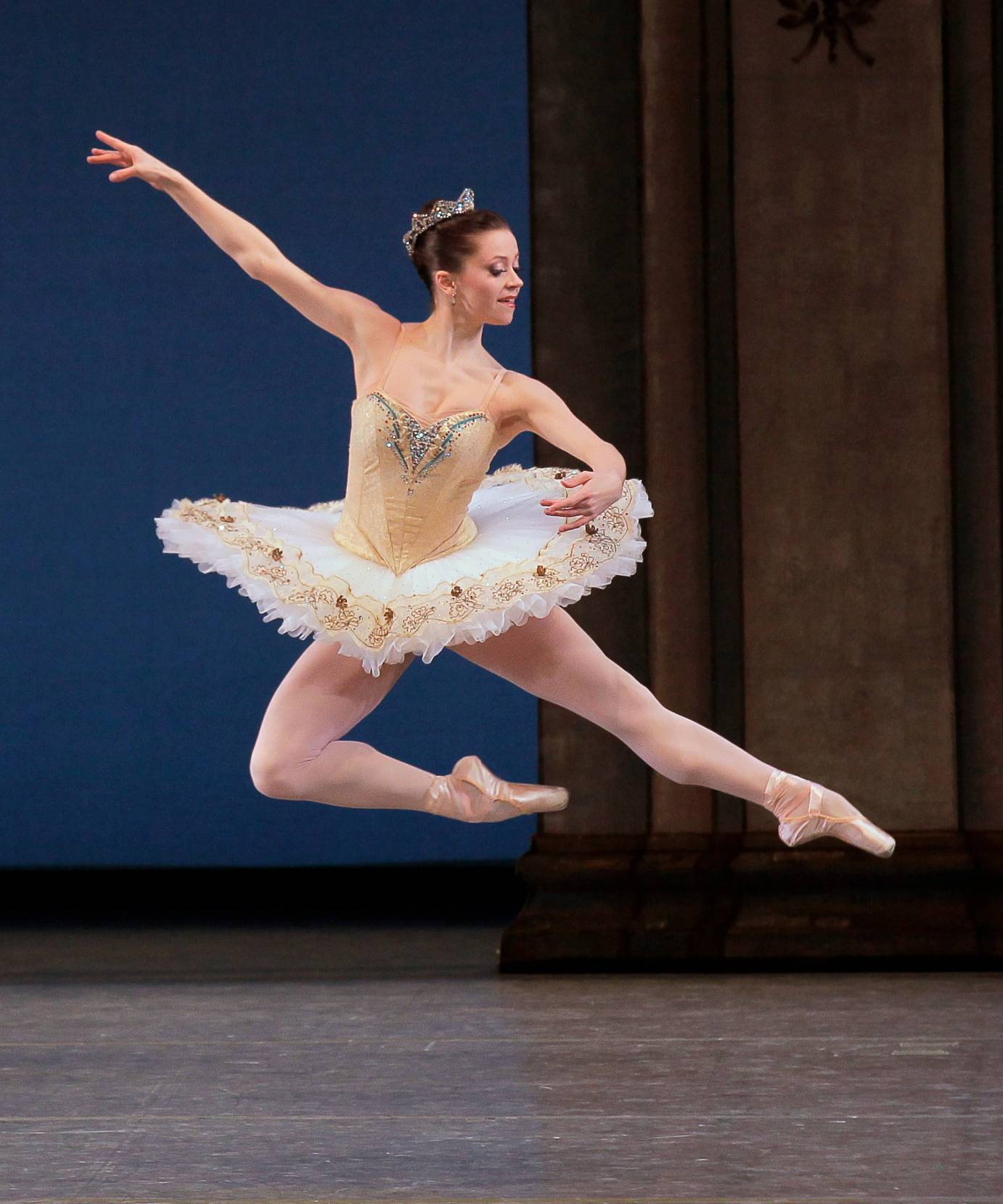 A woman in a gold tutu leaps sideways in profile