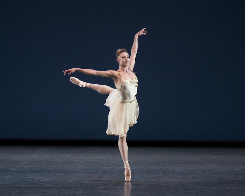 Sara Mearns in a white chiffon dress stands en pointe in attitude position