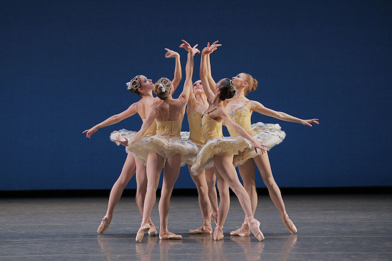 Five ballerinas stand into a circle wearing yellow jewel encrusted tutus. They look into the palm of their right raised arm.