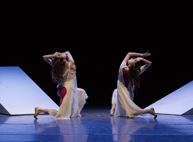 Two dancers in white sheer frocks with red on the backside kneel away from the audience. Their faces are in profile. Upstage of them are two white triangular ramps.