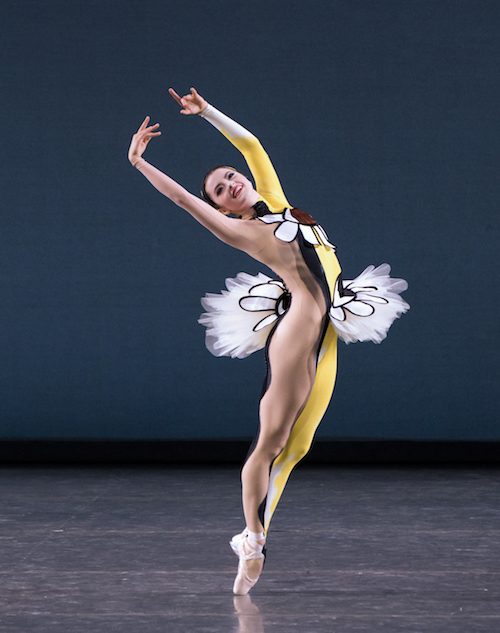 A ballet dancer in a unitard that is nude on one side and yellow and bedazzled on the other.