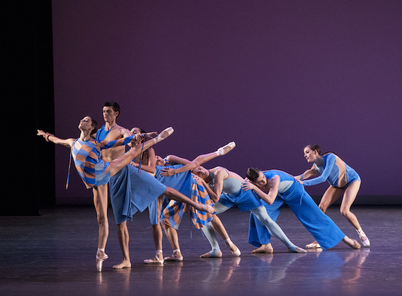 Dancers in blue and orange costumes of various styles are configured in a cascading line