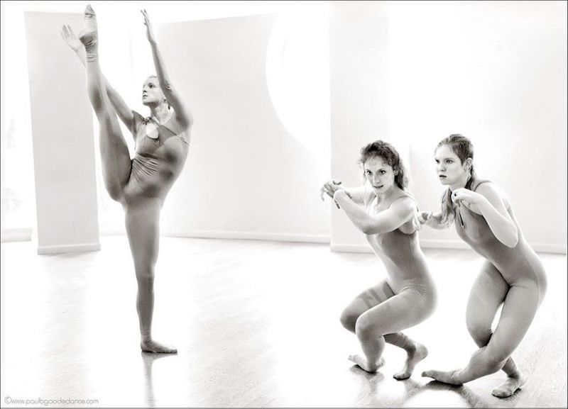 A unitard clad dancer executes a high developpe while two others swivel down to the floor