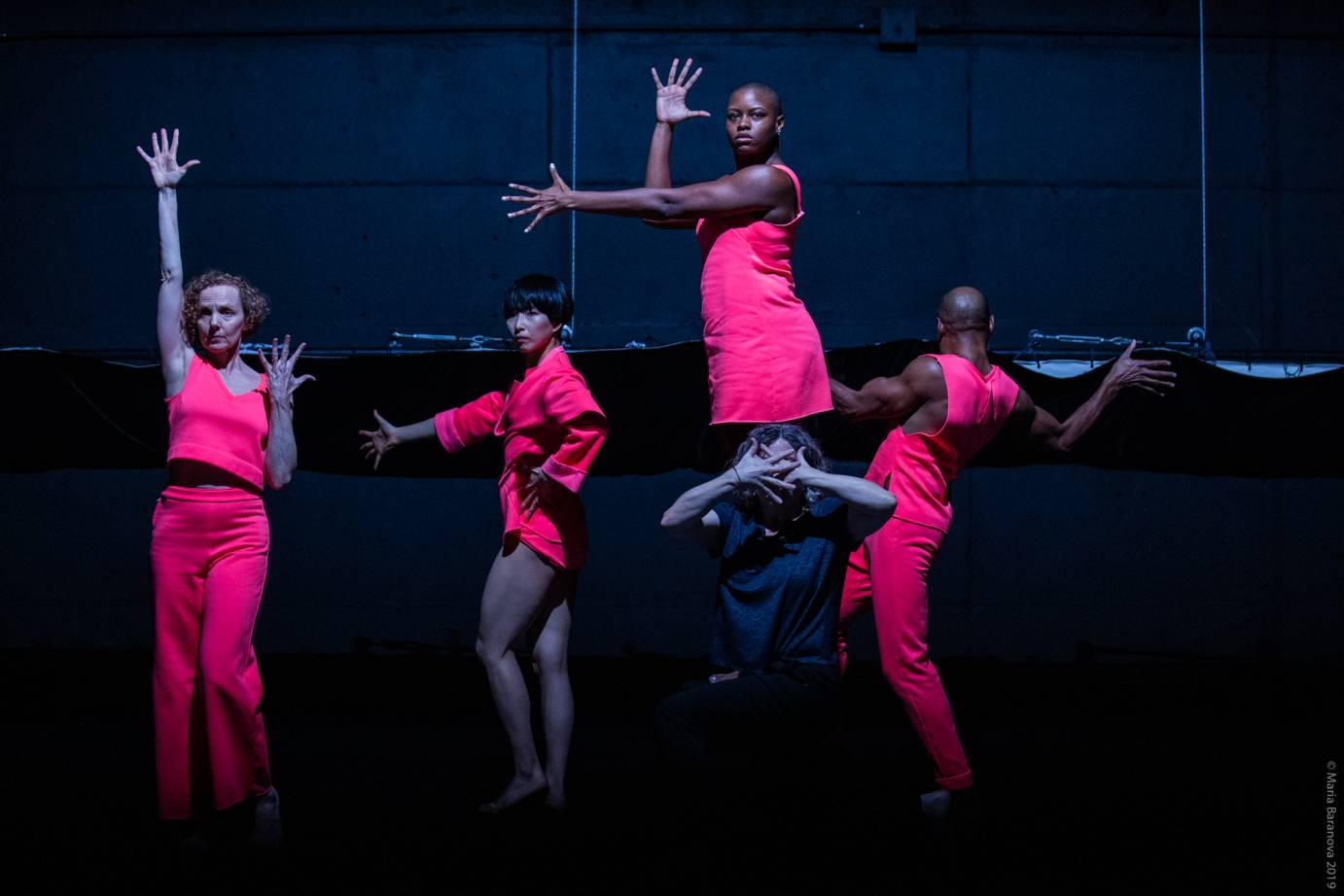 A group in bright pink makes voguing gestures with intense expressions