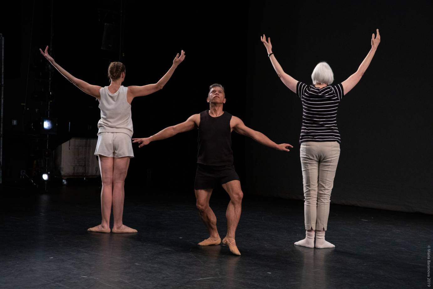 Two women extend their arms in high Vs, backs to audience, while one man extends his arms in a low V
