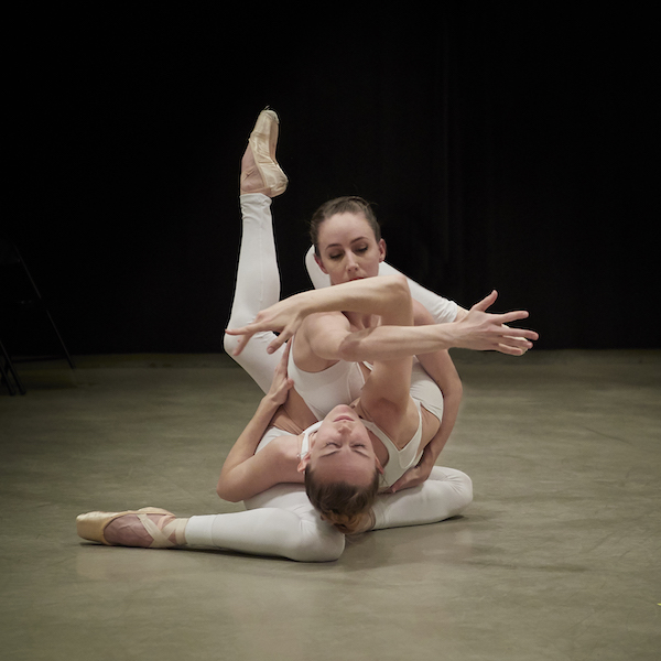 Two female dancers in white are interwined like pretzels on the floor. They both wear pointe shoes.