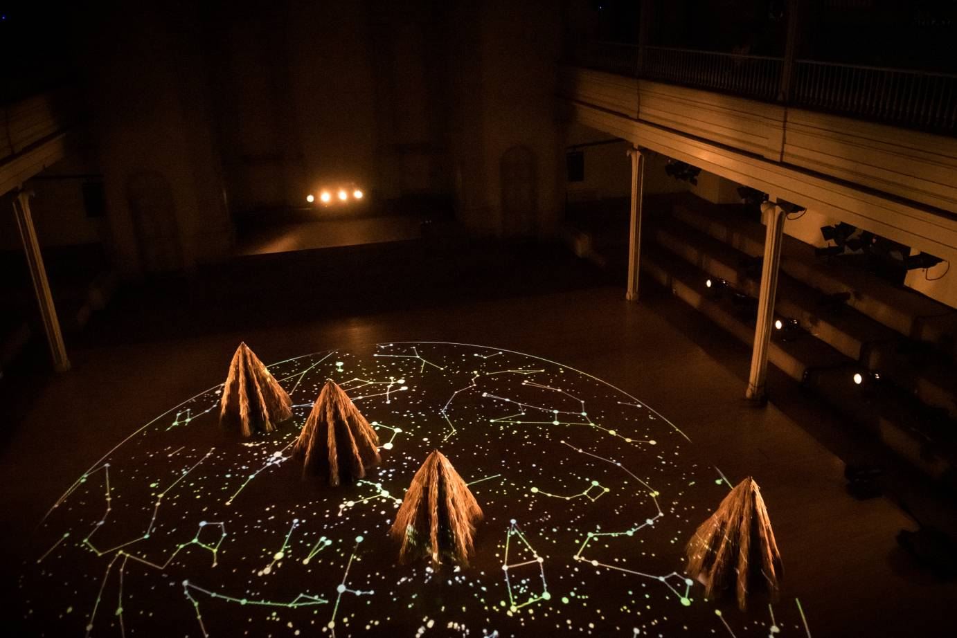 Four dancers with raffia cones covering them stand on a floor illuminated with a projection of stars and constellations