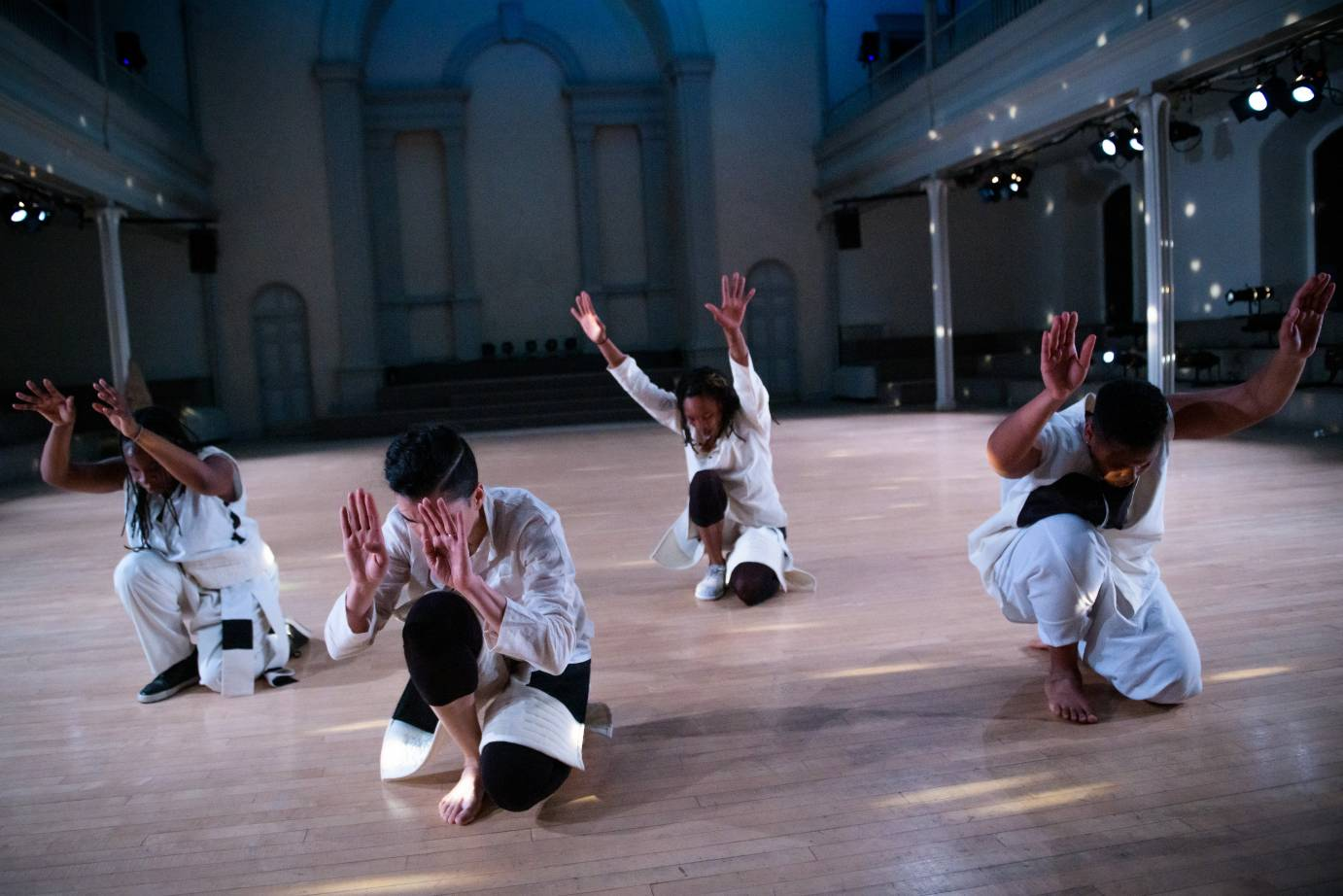 Four dancers in white kneel with their arms extended in front of them