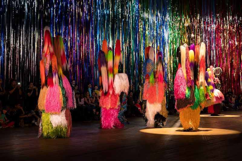 Nick Cave's color Soundsuit performers are enshrouded in his neon raffia, staffs of hair or fur. They stand in front of the mylar streamers.