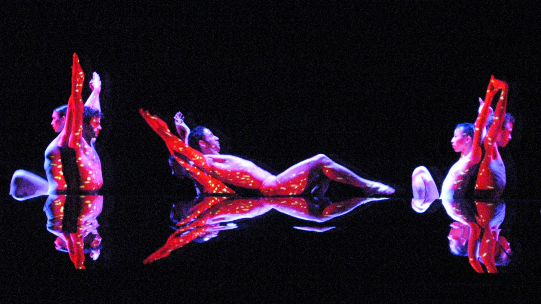 Red and yellow light is projected on dancers' skins as they stand back to back with their arms extended