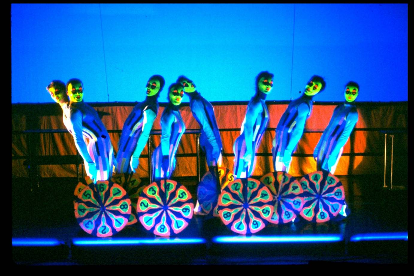 Dancers resembling clowns with neon green faces and standing on or behind pin wheel-looking installations.