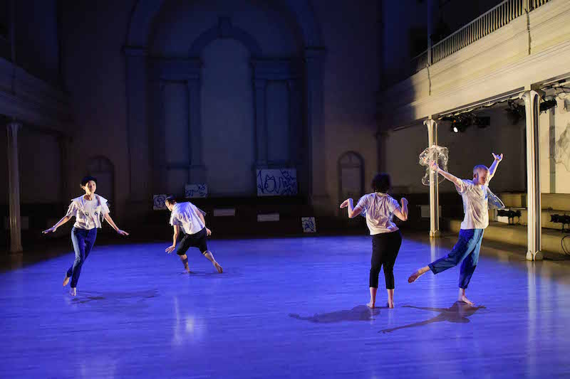 Four dancers in cat t-shirts run around the sanctuary of St. Mark's Church under royal blue lights