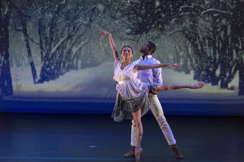 Two dancers pose majestically in white in front of a snowy tree-filled painted backdrop