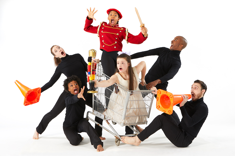 Dancers open their mouths wide as they pretend to tip a shopping cart. Some dancers are holding traffic cones.