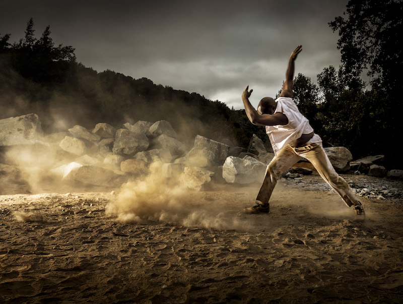 A dancer in all white strikes a pose on the dusty site of Andy Goldsworthy's stone tower project. His arm shields his face as dust swirls around him.