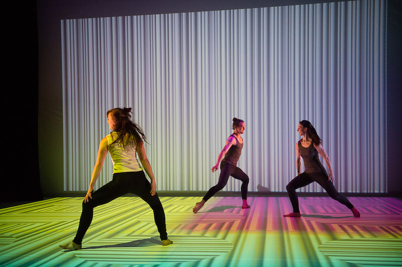 Dancers assume wide positions with bent legs. A pattern of white lines is projected on the back wall and floor