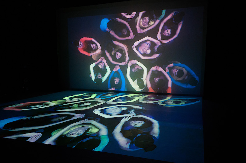 A film of a group of people in bright prints is projected on the back wall of the theater and on its floor