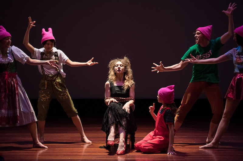 A group of performers pose around the actor who plays the witch. She wears a long black dress and sits in a chair. The others wear colorful casual clothes and Pink Pussie hats.