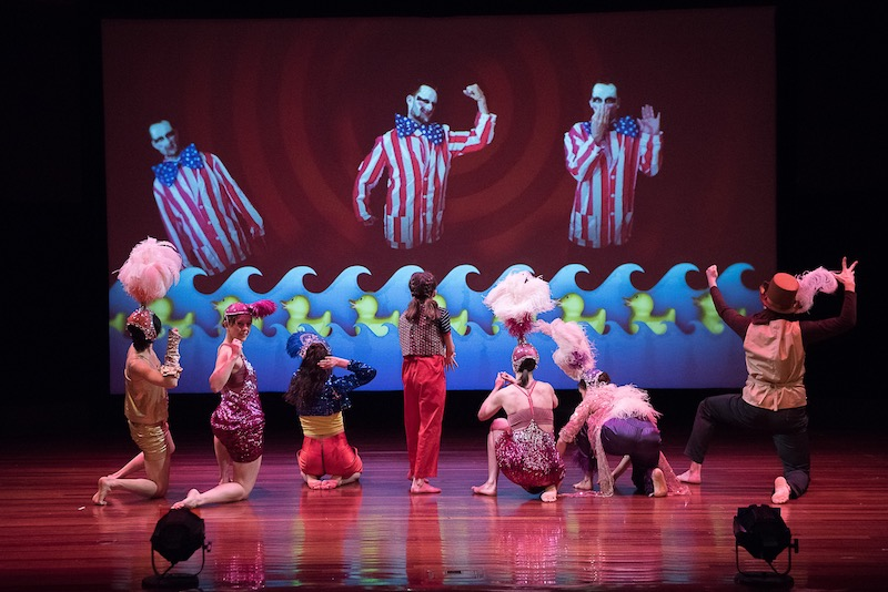 A group of dancers in head-dresses stand on their knee at stare up at a projection that features a man in a Uncle Sam costume.