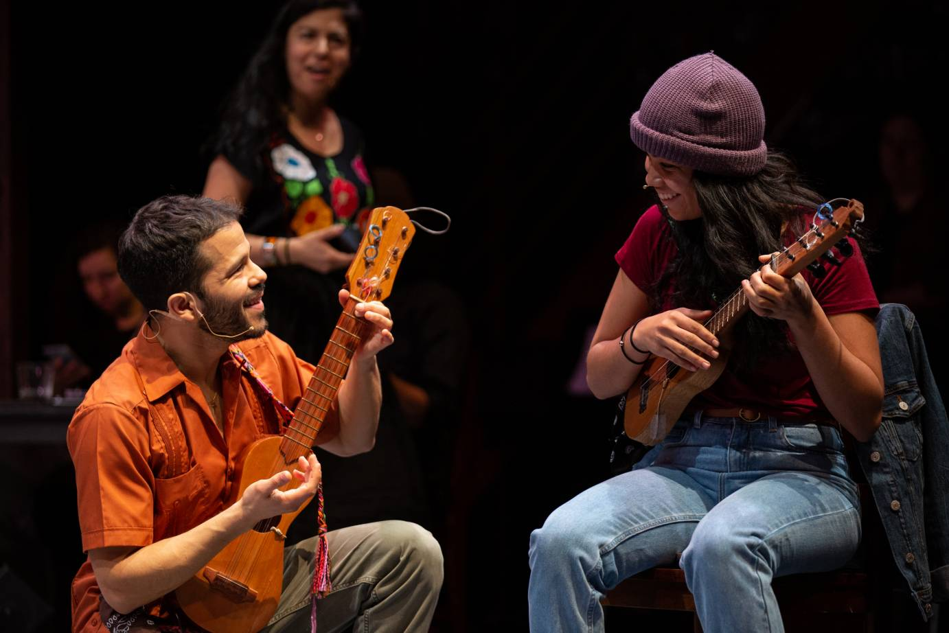 A man and a woman play stringed instruments as they smile at each other