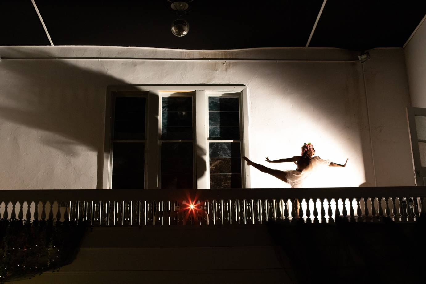 A woman extends her limbs in shadows on a balcony