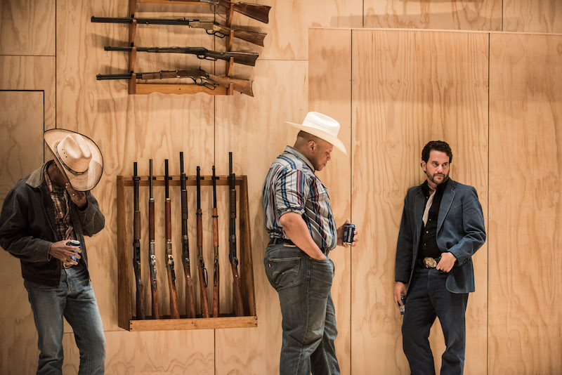 Three men stand against a wood-paneled wall. Two wear Cowboy hats. Rifles are affixed to the wall behind them.