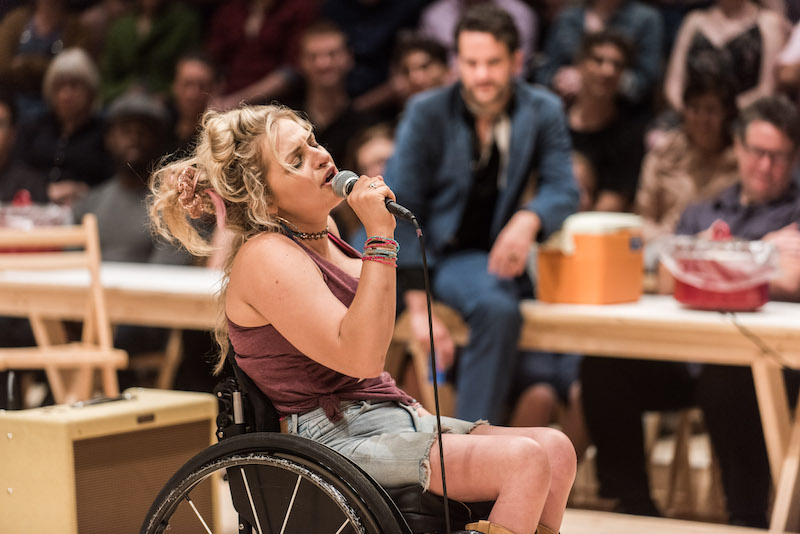 A woman with blonde hair closes her eyes singing into a microphone. She's seated in a wheelchair.