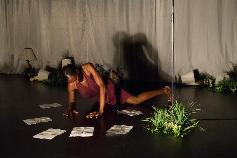 Okwui lays on the ground in a magenta halter dress. Notebook paper and plants litter the flower. Lamps are haphazardly tipped over.